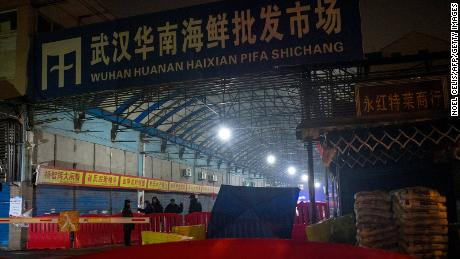 Security guards stand in front of the closed Huanan Seafood Wholesale Market in the city of Wuhan, in the Hubei Province, on January 11, 2020.