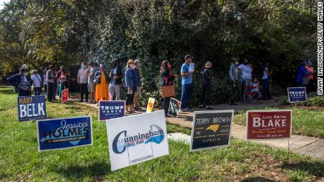 Voters in Charlotte, North Carolina, wait in line to cast their ballots at the West Boulevard branch of the Mecklenburg County library on October 15, 2020, the first day of early voting.