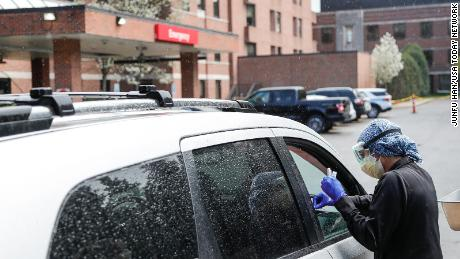 An ER technician tests patients for Covid-19 outside of the emergency entrance of Beaumont Hospital in Grosse Pointe, Michigan, on April 15, 2021