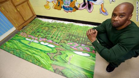 Attica Correctional Facility inmate Dixon poses with his golf art he created in prison.