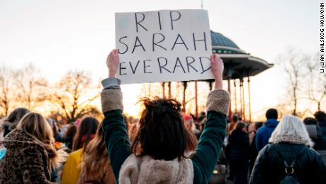 A mourner at the Clapham Common bandstand holds a sign as part of a vigil for Sarah Everard, a 33-year-old woman, whose killing has reignited a national debate on women's safety and sexual assault.