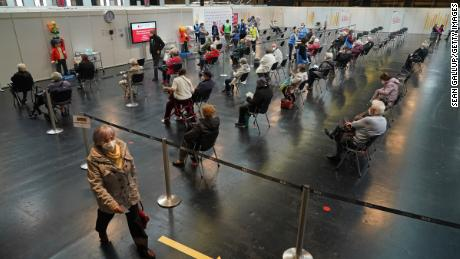 Patients sit in a monitoring area after receiving a Covid-19 shot at the Arena Berlin mass vaccination center on April 15, 2021 in Berlin, Germany.