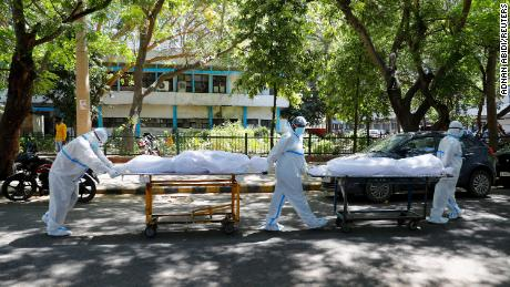 Health workers wearing personal protective equipment  carry bodies of people who were suffering from Covid-19 outside the Guru Teg Bahadur hospital, in New Delhi, India, on April 24.