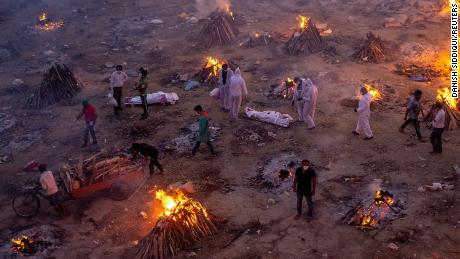 People wait to cremate bodies at a crematorium ground in New Delhi on April 23.
