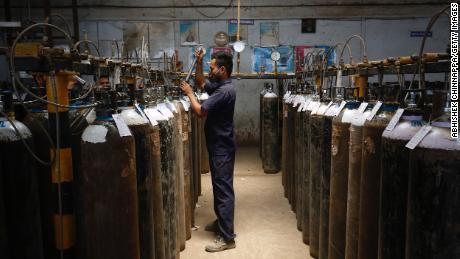 An employee fills oxygen cylinders in Bengaluru, India.
