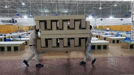 Workers carry biodegradable cardboard beds in a makeshift ward at the Sardar Patel Covid Care Centre and Hospital in New Delhi, India, on April 24, 2021.