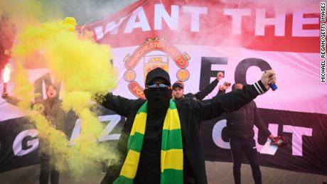 Fans are seen protesting Manchester United's Glazer ownership outside the stadium.