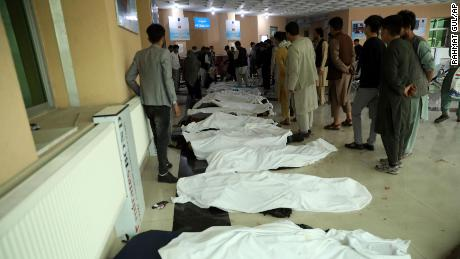 Afghan men try to identify the dead bodies at a hospital after a bomb explosion near a school west of Kabul, Afghanistan on Saturday.