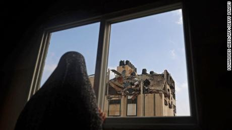 A Palestinian woman looks at the rooftop of a building which was hit by an Israeli airstrike at al-Shati Refugee Camp in Gaza City on Tuesday.