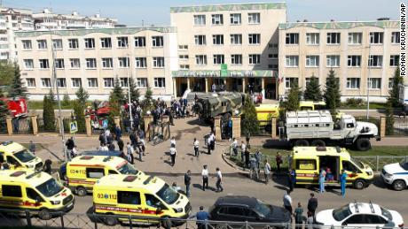 Ambulances and police cars are parked at a school after a shooting in Kazan, Russia.