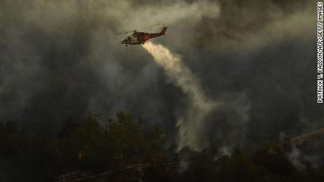 Firefighters keep a lookout as a Los Angeles Fire Department helicopter makes a water drop Saturday on the Palisades Fire in Topanga State Park.