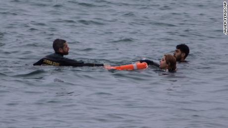 A Guardia Civil officer rescues people from the water.