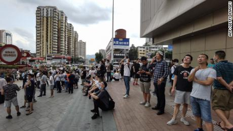 Shoppers look up at the SEG Plaza in Shenzhen after being evacuated from the wobbling building.