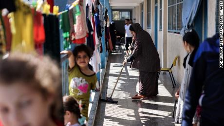 A displaced Palestinian woman cleans outside classrooms that are being used to host families who fled their homes for safety at a school in Gaza City on May 18.