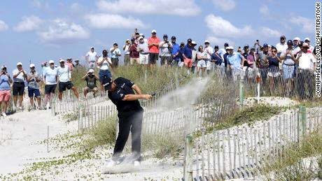 Lowry hits his second shot to the 16th hole from the beach after his tee shot went right and into the dunes.
