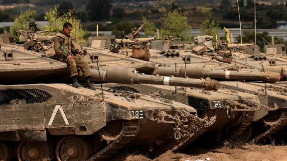 An Israeli soldier sits on top of a tank at a staging ground near the border with Gaza on Friday following the ceasefire agreement.