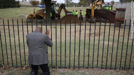 The Rev. Robert Turner prays as crews conduct a test excavation in October.