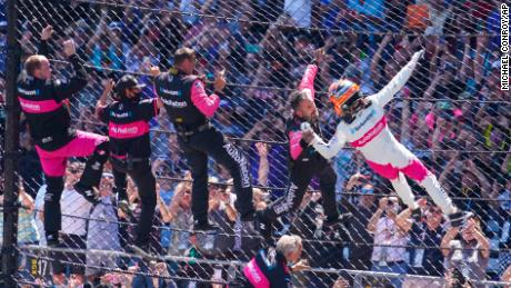 Helio Castroneves of Brazil celebrates with his team as he climbs the fence at the start/finish line after winning the Indianapolis 500 auto race at Indianapolis Motor Speedway in Indianapolis, Sunday, May 30, 2021.