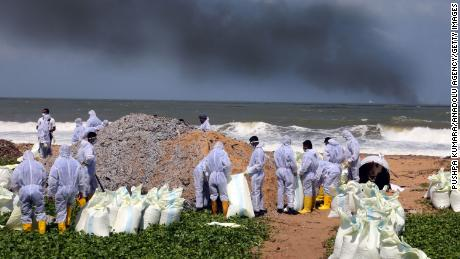 Sri Lanka Navy personnel remove waste washed ashore from the burning cargo vessel MV X-Press Pearl on the beaches of Wattala to Negombo in the suburbs of Colombo, on May 28.