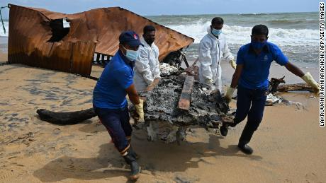 Members of the Sri Lankan Navy remove washed debris from Singapore-registered container ship MV X-Press Pearl.