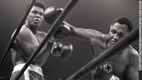 """Muhammad Ali takes a shot from Joe Frazier during their heavyweight match which was coined """"The Fight of the Century""""."""