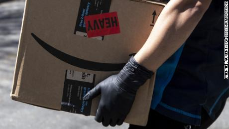 An Amazon delivery woman delivers packages amid the coronavirus pandemic in Los Angeles, California, in March 2020.