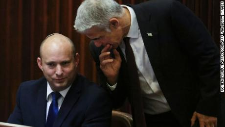 """Right-wing Bennett described centrist Yair Lapid (R), his new coalition partner, as his """"friend."""""""