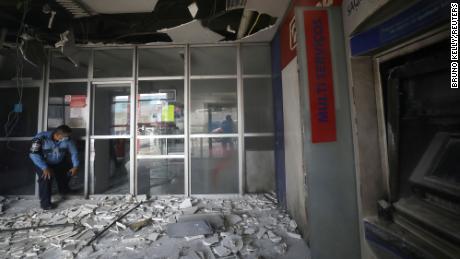 A police officer checks a branch of Bradesco bank damaged in Manaus, Brazil, June 6, 2021.