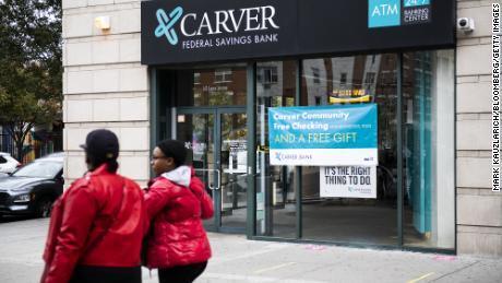 Pedestrians walk past a Carver Federal Savings Bank branch in the Harlem neighborhood of New York, U.S., on Oct. 27, 2020.