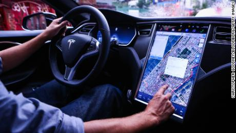 A driver uses the map navigation feature on a touchscreen control panel just prior to the Tesla Motors 8.0 software update inside a Model S P90D.