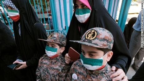 A mother and her children wearing the Islamic Revolutionary Guard Corps;  Uniform, line up at the polling station on Friday.