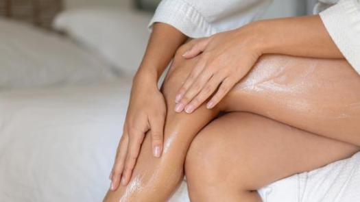 Woman applying cream on her legs