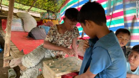 Fearing an attack from Myanmar military, refugee children from villages in Chin state spend time playing homemade checkers.