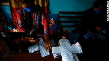 A volunteer stitches cloth to make reusable sanitary pads at Sinamangal in Kathmandu, Nepal.