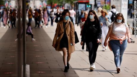 Pedestrians wearing face masks walk on Oxford Street in central London on June 6.