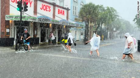 Determined visitors head to Sloppy Joe's bar while crossing a flooded Duval Street in Key West.