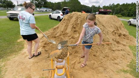 Emma Barlow, 9, works with her mother Brandi Barlow to fill sandbags Tuesday in Middleburg.