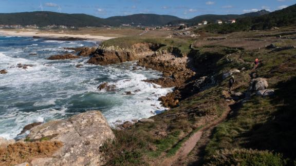 Hikers follow the lighthouse trail, Camiño dos Faros, near Traba Beach and the town of Laxe.