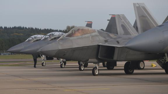 A US Air Force F-22 Raptor lines up next to three F-15E Strike Eagles at Royal Air Force Lakenheath, England, in 2017.