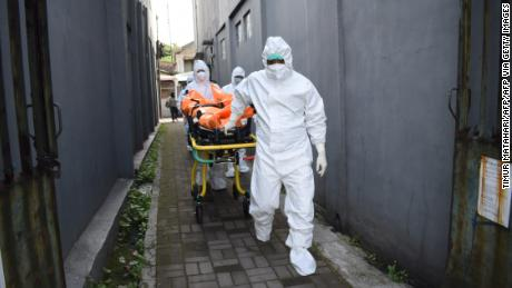 Health workers remove the body of a Covid-19 victim who died while isolating at home in Indonesia on Wednesday.