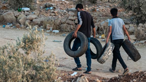 Young Palestinian men carrying tires ready to set them alight, in Beita, West Bank, on July 2.