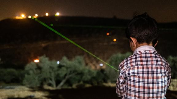 A Palestinian boy shines a green laser at the illegal settlement of Givat Evyatar, West Bank, on July 2.
