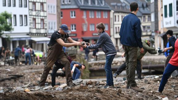 People collect debris in Bad Muenstereifel, Germany.