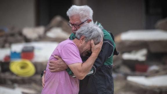 Two brothers embrace Monday, July 19, in front of their parents' home, which was destroyed by flooding in Altenahr, Germany.