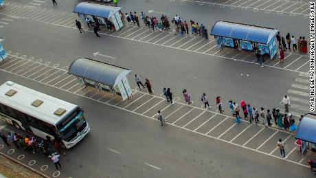 People wait for buses at a bus station in Kigali, capital city of Rwanda, on July 1.