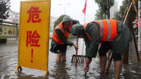 Workers drain water from a waterlogged area in Lanzhou, Henan, China, on July 20.