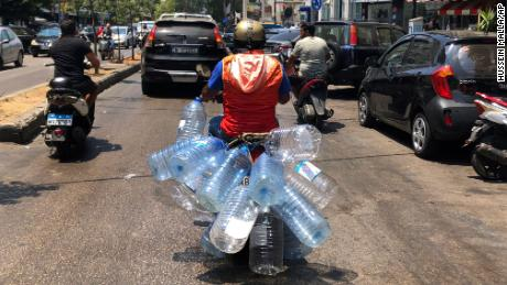 A man rides his scooter with empty water bottles to fill them with gasoline, in Beirut, on June 23, 2021.