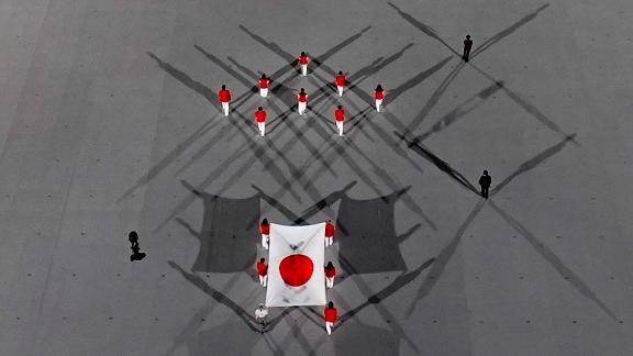 The Japanese flag is carried during the opening ceremony. After the Japanese National Anthem was sung, a moment of silence was called to remember the global victims of the Covid-19 pandemic.