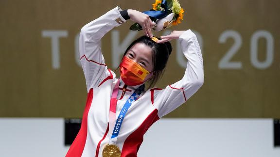 China's Yang Qian, the first gold-medal winner of these Olympics, celebrates on July 24. She finished first in the 10-meter air rifle.