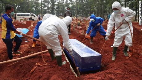 Workers in protective gear lower a coffin of a Covid-19 victim to a grave for burial at the Cipenjo Cemetery in Bogor, West Java, Indonesia, on July 14, 2021.
